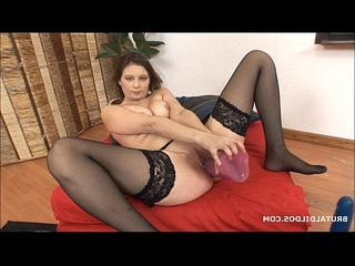 Brunette babe sucks on a big dildo as another gapes her wet pussy